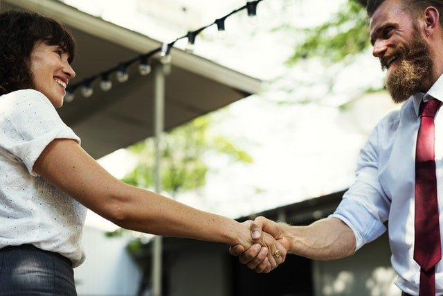 assertive and decisive man and woman shaking hands at meeting